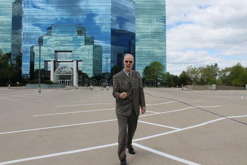 Business Man Celebrating in front of Mirrored Building royalty free stock image