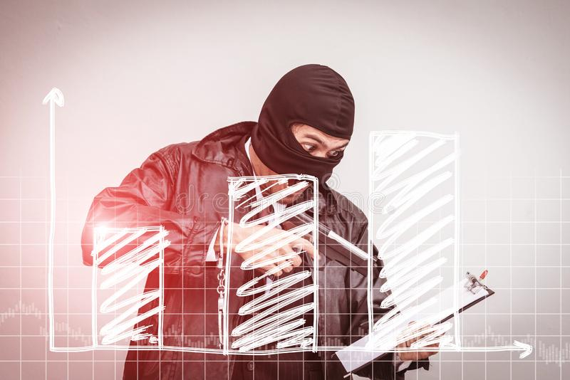 A man wearing a suit, wearing a robber, carrying a gun, ready to go out to rob,Business down concept stock photo