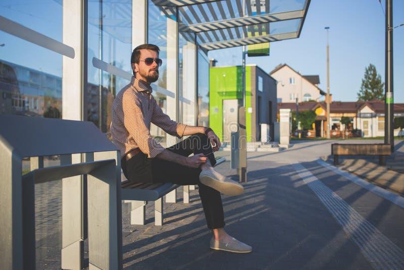 Man Wearing Sunglasses Sitting at Bus Stop during Daytime royalty free stock photos