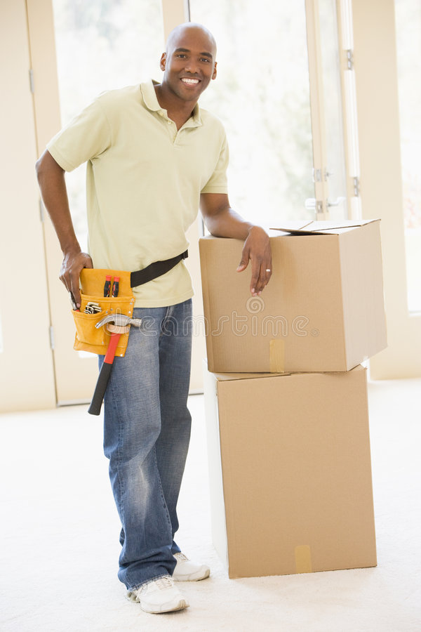 Man wearing tool belt by boxes in new home royalty free stock image