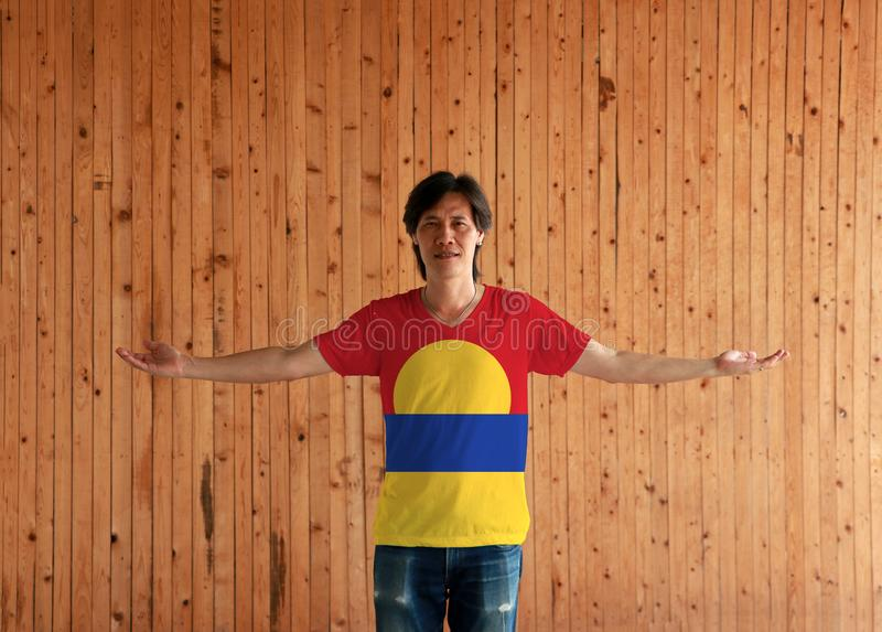 Man wearing United States Minor Outlying Islands flag color shirt and standing with arms wide open on the wooden wall background. Red blue and yellow color royalty free stock photography
