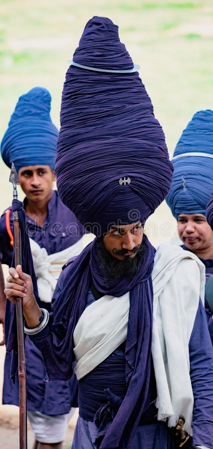 Man wearing a very large blue turban to the Hola Mahalla festival is followed by two acolytes royalty free stock photography