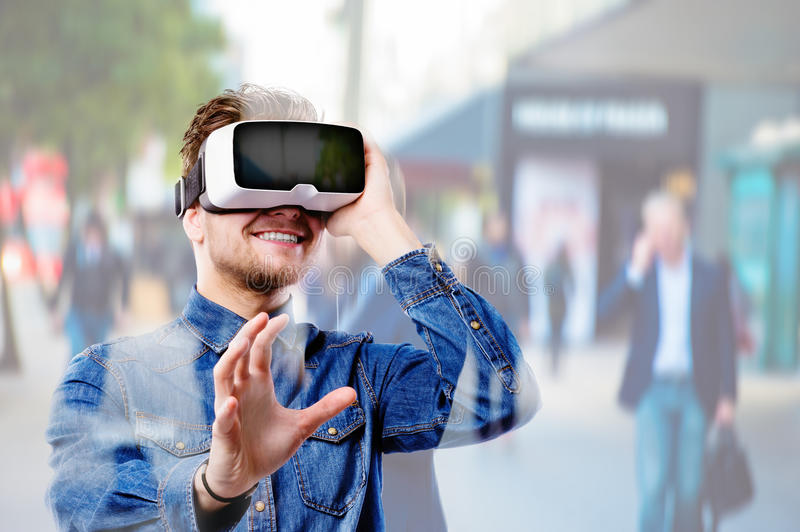 Man wearing virtual reality goggles. Crowded street of London. Hipster man in denim shirt wearing virtual reality goggles. Crowded street of London stock image