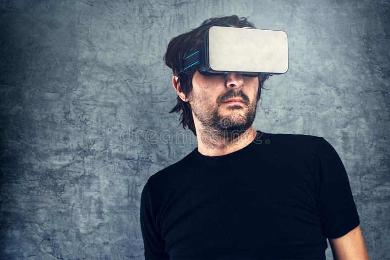 Man wearing virtual reality goggles for 3d VR multimedia content. Adult Man wearing virtual reality goggles for 3d VR multimedia content, modern futuristic stock photography