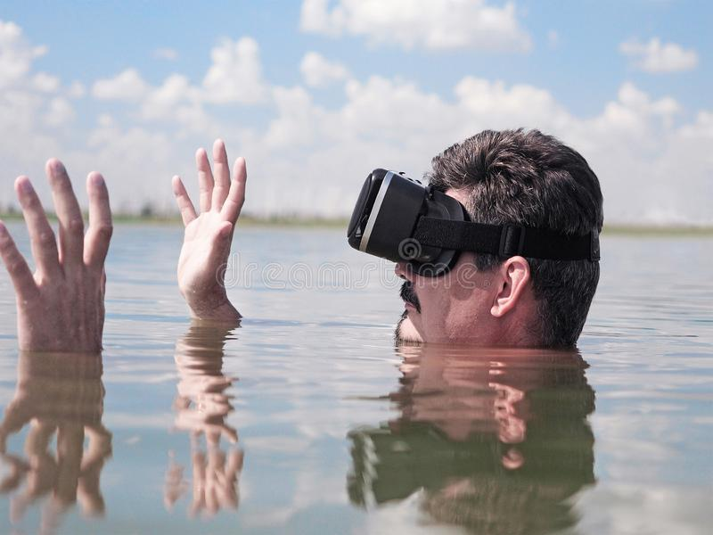 Man wearing virtual reality goggles lies  in water stock images