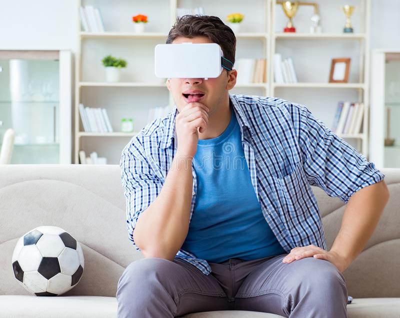 Man wearing virtual reality VR glasses watching soccer football. The man wearing virtual reality vr glasses watching soccer football stock photos