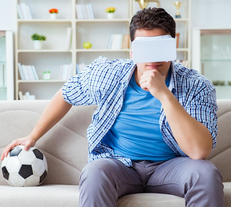 Man wearing virtual reality VR glasses watching soccer football. The man wearing virtual reality vr glasses watching soccer football stock images