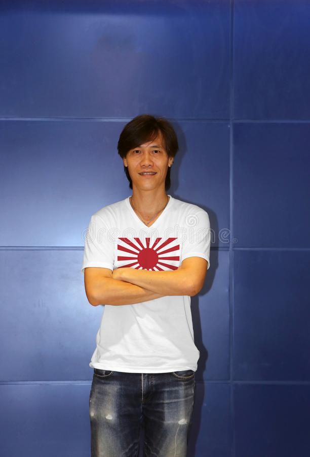 Man wearing war flag of the Imperial Japanese Army on white shirt and cross one`s arm on the blue wall background stock photography