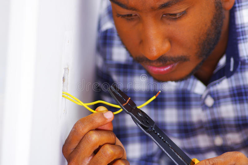 Man wearing white and blue shirt working on electrical wall socket wires using screwdriver, electrician concept stock images