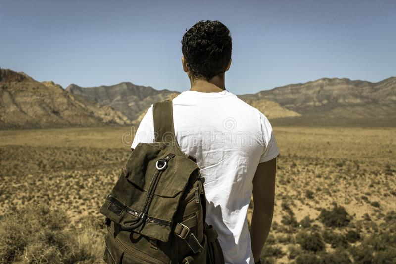 Man Wearing White Crew Neck T-shirt And Gray Backpack Standing By The Desert During Daytime Free Public Domain Cc0 Image