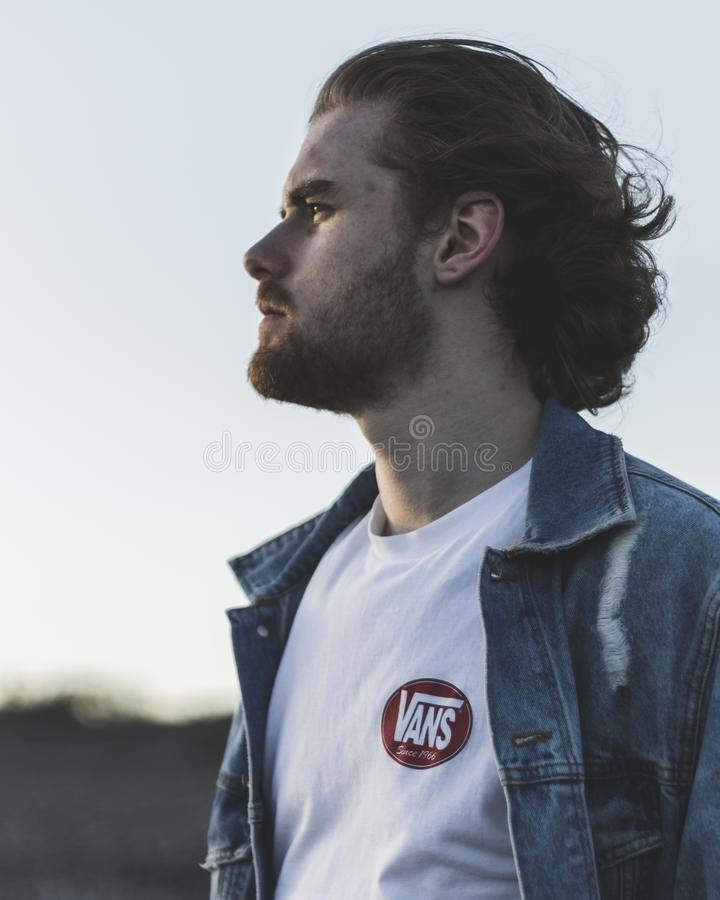 Man Wearing White Crew-neck Vans Top and Blue Denim Button-up Jacket stock images