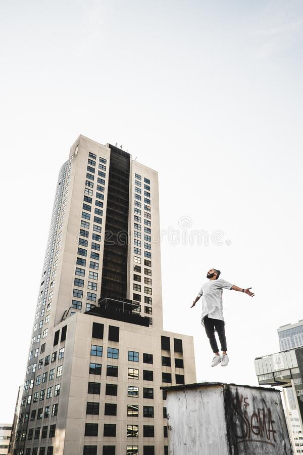 Man Wearing White Long Sleeve Shirt Beside White and Black High Rise Building stock photos