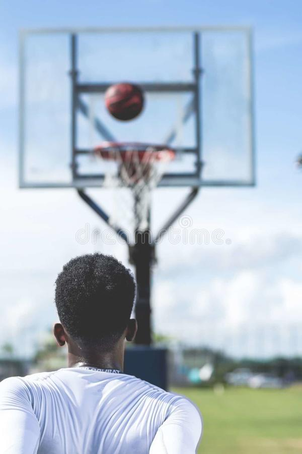 Man Wearing White Long-sleeved Shirt Near Basketball Hoop royalty free stock photography