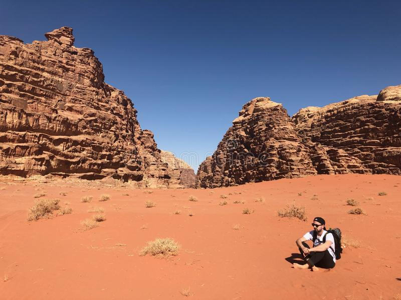 Man Wearing White Shirt and Black Pants Sitting on Soil Behind Rock Formation Mountain stock photography