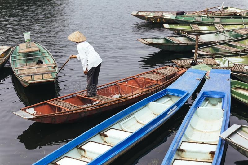 Man wearing white shirt, conical hat with his paddle stand on red empty rowing boat with many boats stop over the river. royalty free stock photos