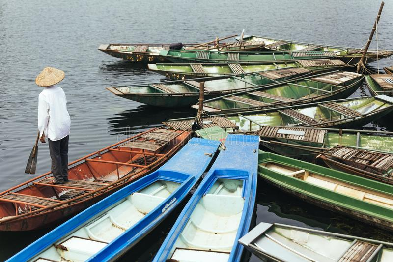 Man wearing white shirt, conical hat with his paddle stand on red empty rowing boat with many boats stop over the river. stock images