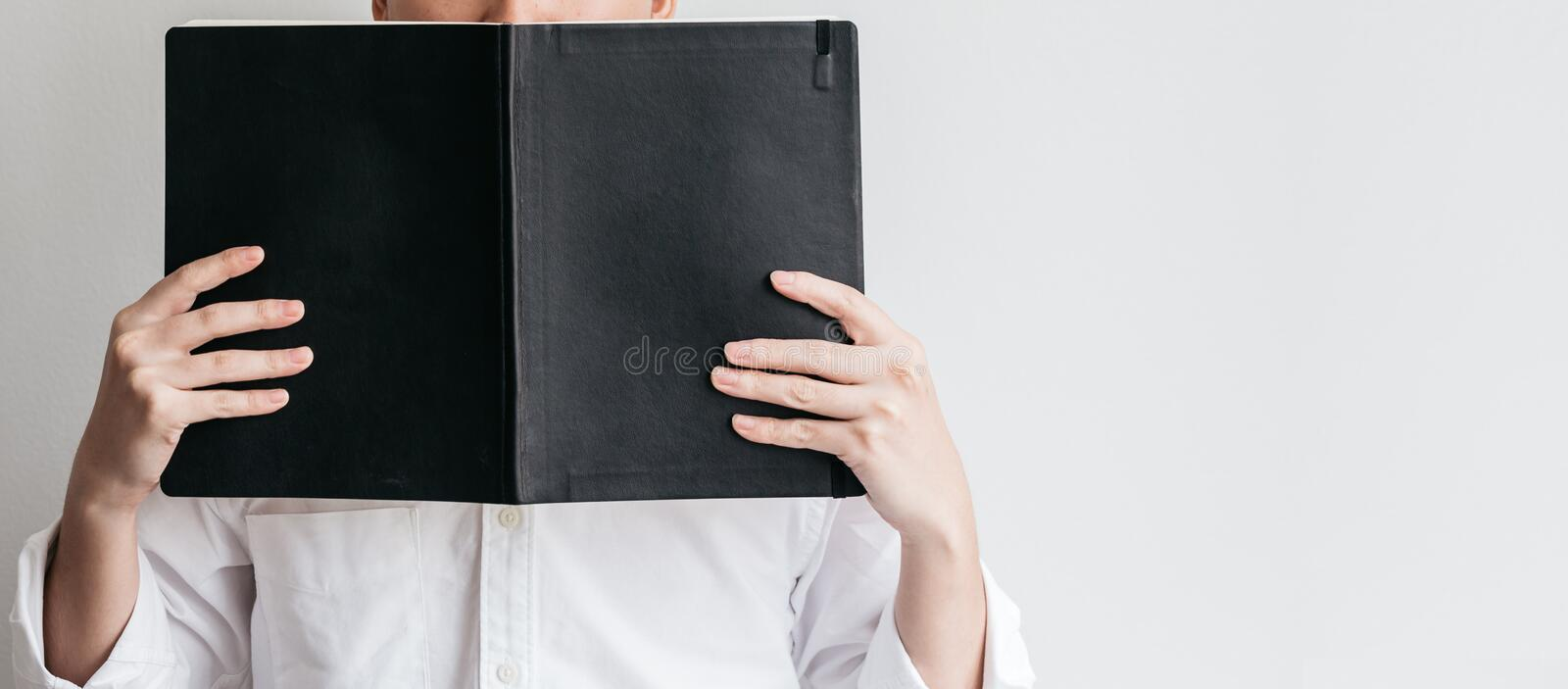 Man wearing white shirt and holding a black cover book in front of him on the left side with copy space stock photos