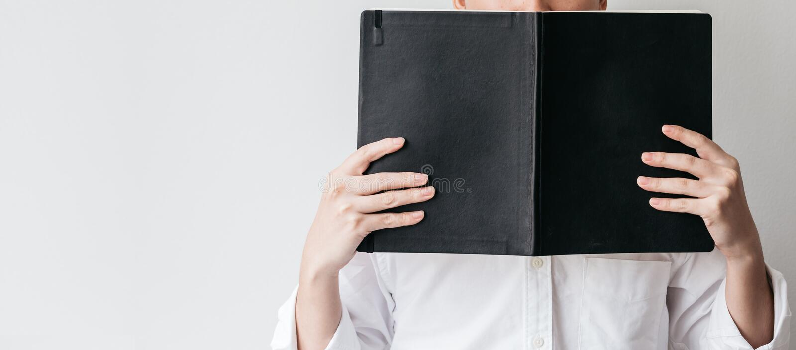Man wearing white shirt and holding a black cover book in front of him on the right side with copy space stock images