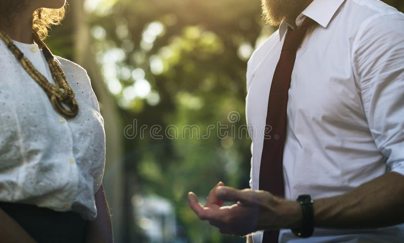 Man Wearing White Shirt Holding Out Hand in Front of Woman in White Lace Top royalty free stock image