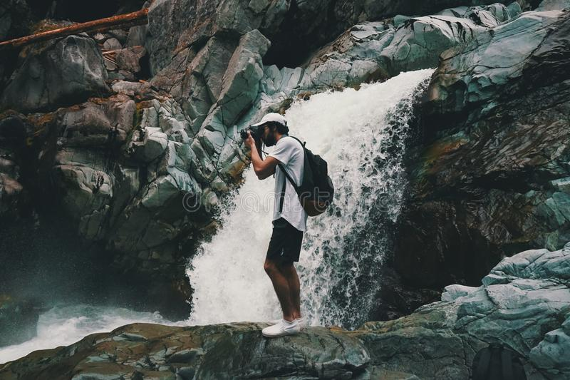 Man Wearing White T-shirt Holding Dslr Camera Near Waterfall royalty free stock images