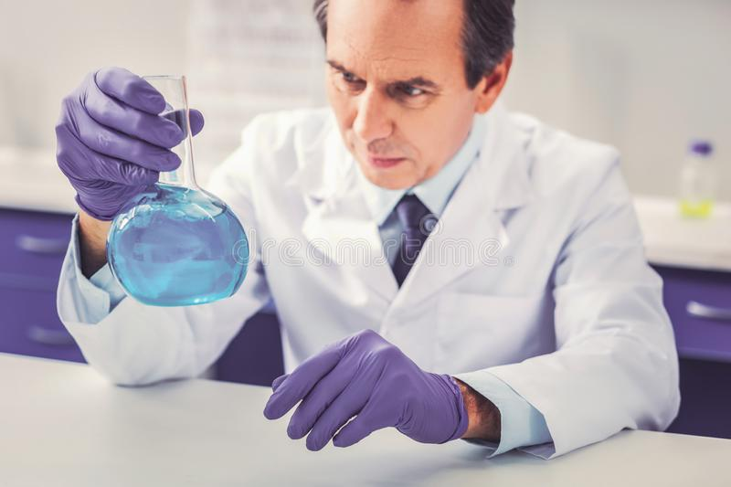 Man wearing white uniform working in laboratory. White uniform. Skillful professional man wearing white uniform feeling involved in working in modern laboratory royalty free stock images