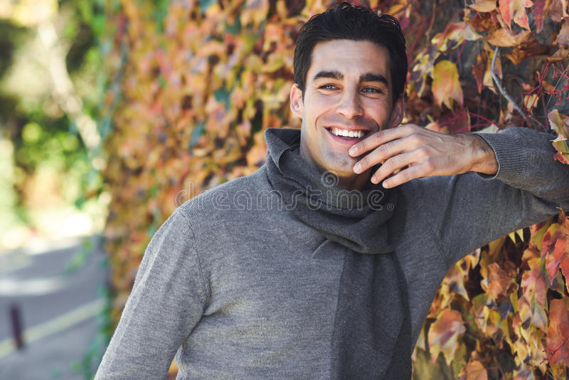 Man wearing winter clothes smiling in autumn leaves background stock photos