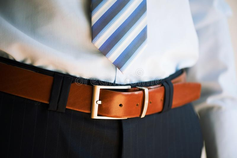 Man wears belt. Young businessman in casual suit with accessories. Fashion and clothing concept. Groom getting ready in. Morning before ceremony royalty free stock photos