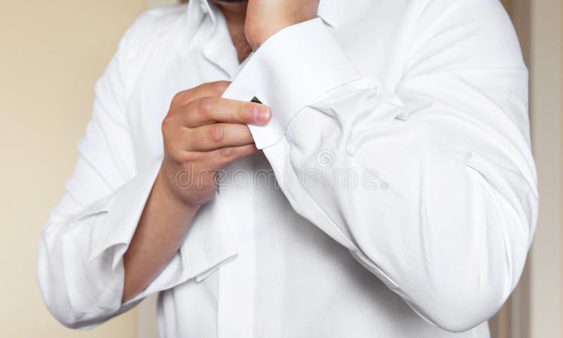 Man wears white shirt and cufflinks. Groom wears white shirt and cufflinks stock photo