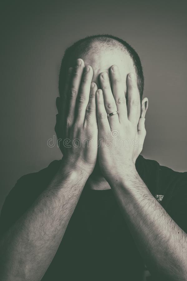 Man with a wedding ring covering his face with his hands royalty free stock photography