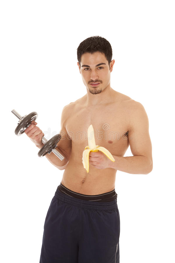 Man with weight and banana. A man is holding a weight in one hand and a banana in the other with his shirt off royalty free stock images