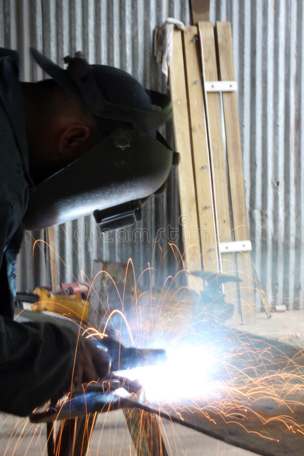 Man Welding. A piece of iron on a work table royalty free stock image