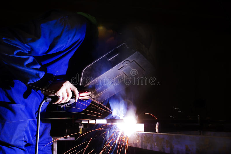 Man welding with mask. Young man in blue welding with mask stock photography