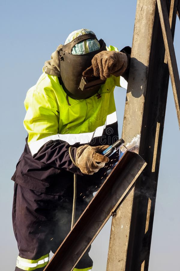 Man welding metal on a construction site, Tradesman working with royalty free stock photos