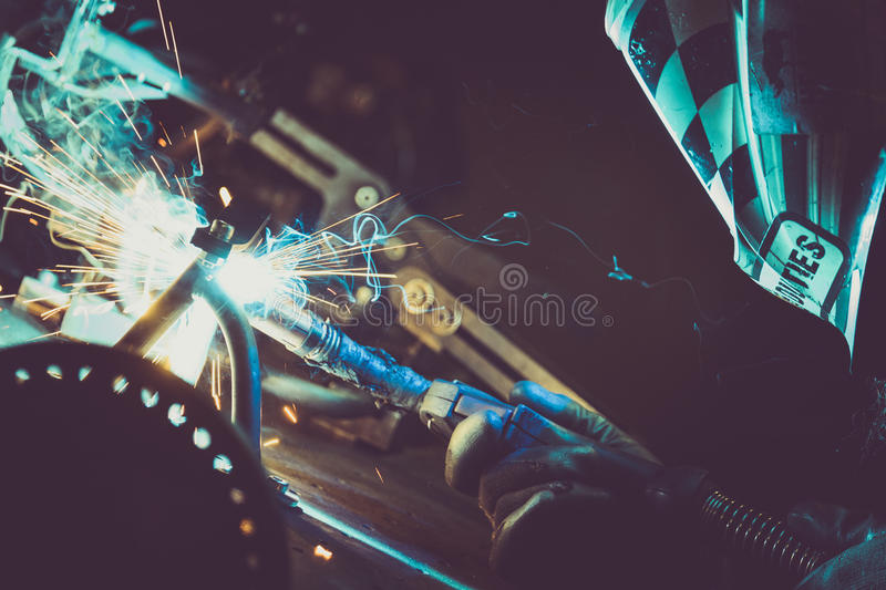 Man welding steel pipe on a work table in an Industrial workshop, producing blue and green smoke, hot sparks. Horizontal photo stock images