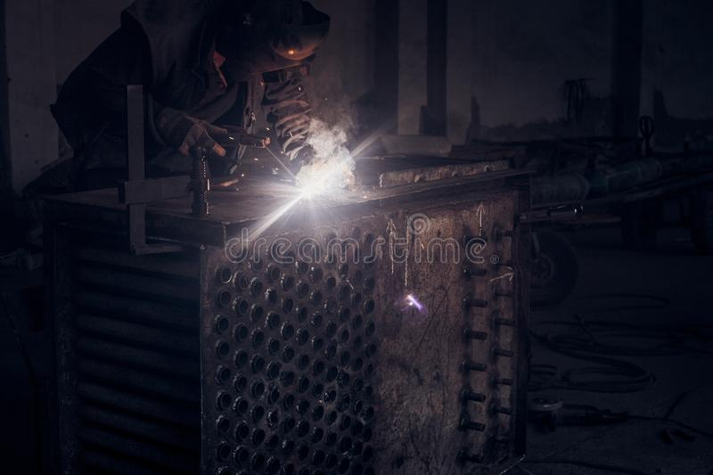 Man welds metal. Worker welding steel in industry with safety mask safety gloves and safety equipment. Metal industry welding royalty free stock image