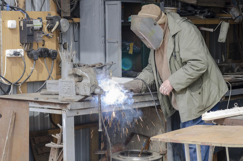 Man welds welding iron parts . stock photo