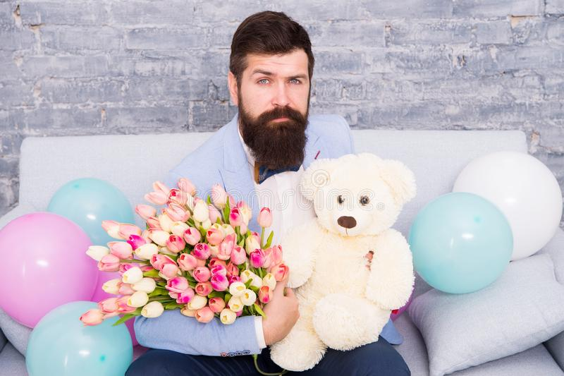 Man well groomed wear tuxedo bow tie hold flowers tulips bouquet and big teddy bear toy. Invite her dating. Romantic. Gift. Romantic man. Macho getting ready stock image