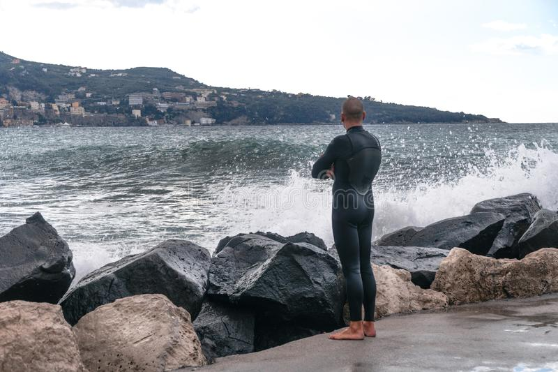 Man in a wet suit, surfer, standing on the shore and looking at the waves in the background of the mountain, Sorrento Italy royalty free stock photo