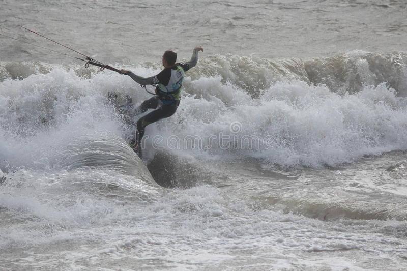Man in Wetsuit Surfing With Parachute, England, September 2105. Silhouette of man skilfully manipulating surfboard against waves, using parachute to give royalty free stock image