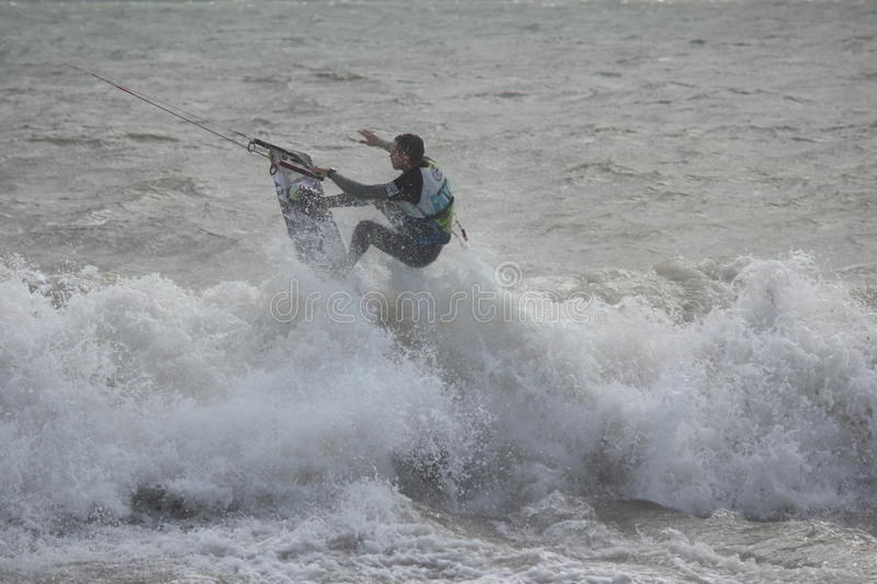 Man in Wetsuit Surfing With Parachute, England, September 2105. Silhouette of man skilfully manipulating surfboard against waves, using parachute to give royalty free stock photo