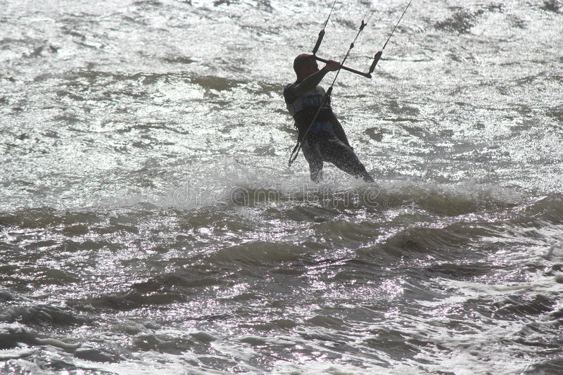 Man in Wetsuit Surfing With Parachute, England, September 2105. Silhouette of man skilfully manipulating surfboard against waves, using parachute to give royalty free stock photos