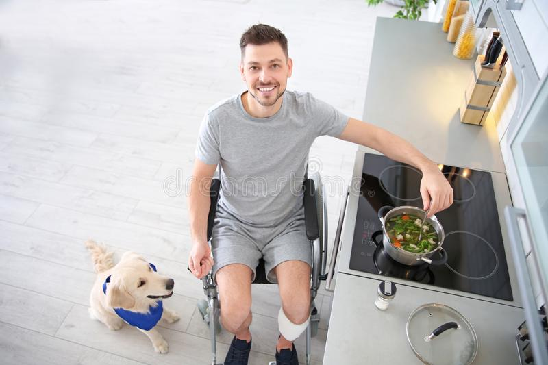Man in wheelchair cooking with service dog by his side royalty free stock photography