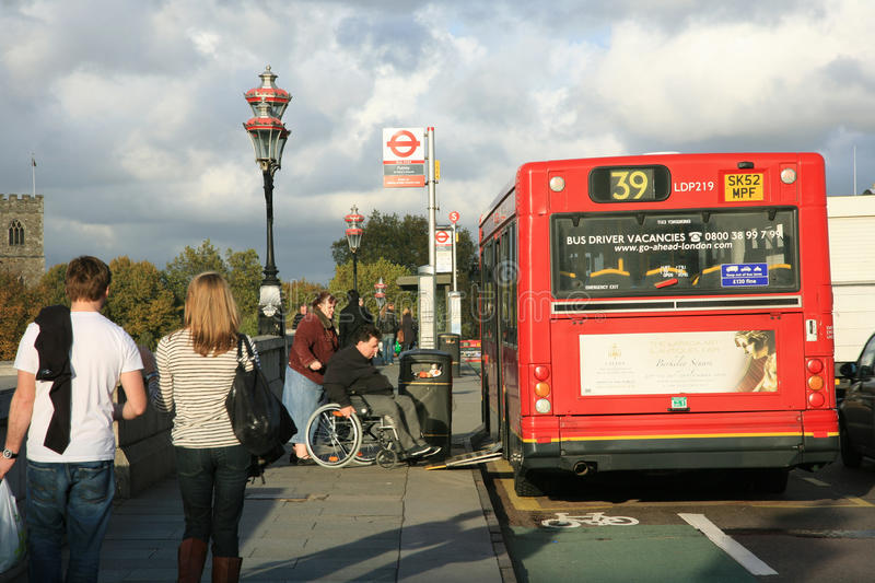 Man in a wheelchair getting on a public bus royalty free stock photos
