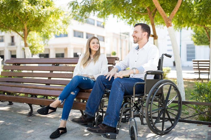 Man in wheelchair with his girlfriend royalty free stock images