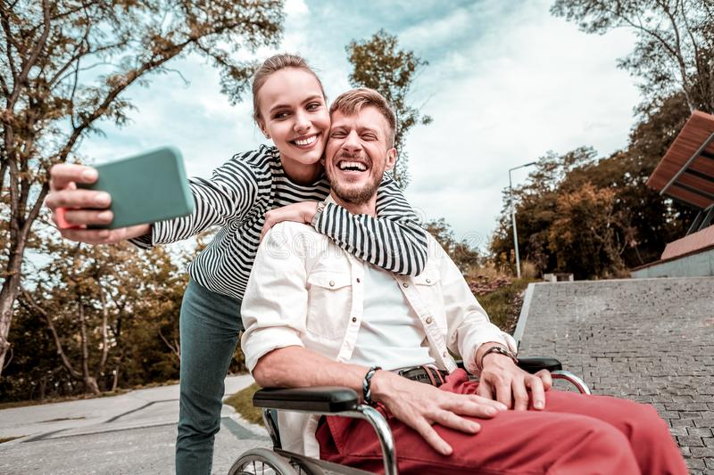 Man in wheelchair laughing while cute girlfriend taking selfie with him royalty free stock photo