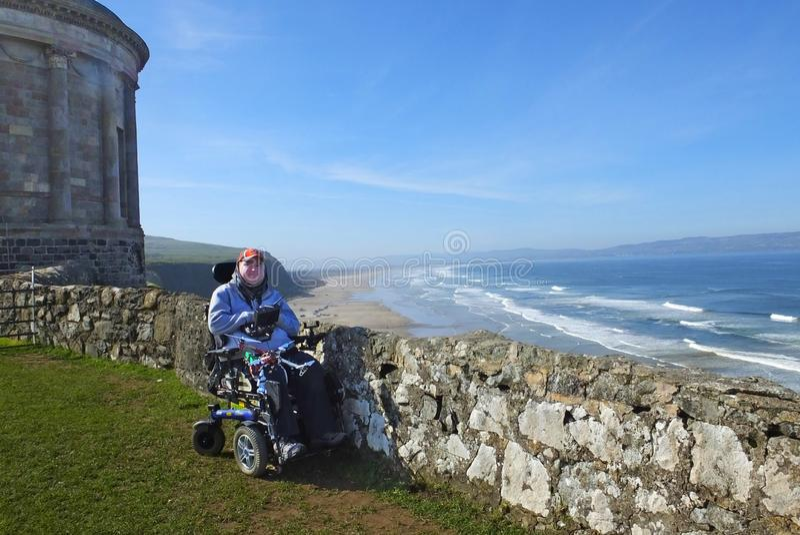 Man in a wheelchair at Mussenden Temple benone beach Co Derry Londonderry Northern Ireland. Man in wheelchair at Mussenden Temple benone beach Co Derry stock photos