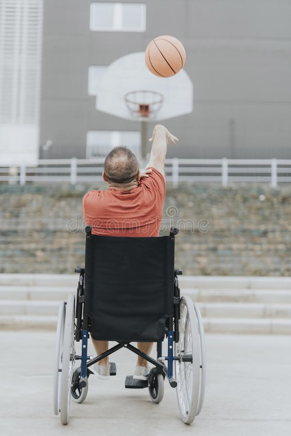 man in a wheelchair plays basketball alone in a city park stock photos