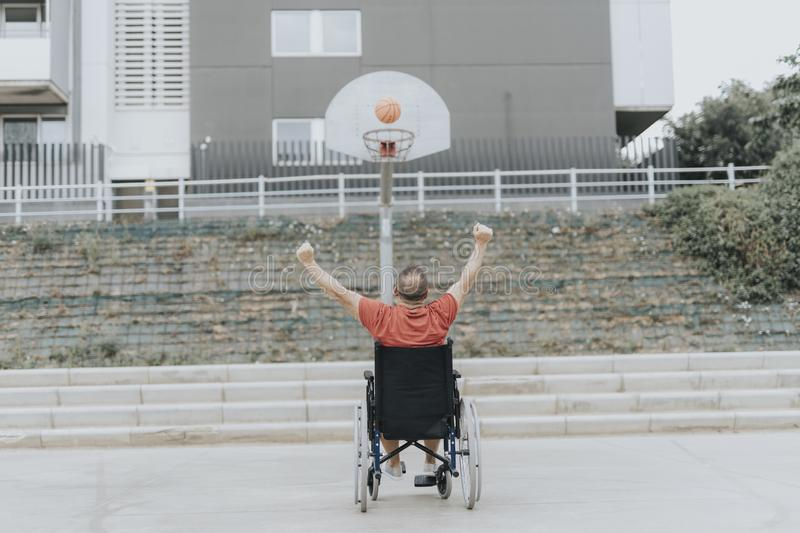 man in a wheelchair plays basketball alone in a city park royalty free stock photo