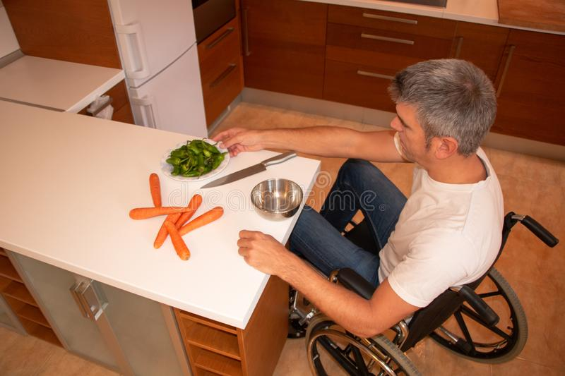 A man in a wheelchair preparing food in the kitchen stock photos