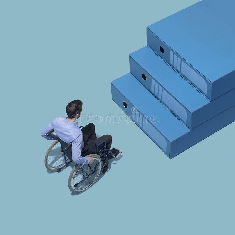 Man in wheelchair stopping in front of a staircase made of folders. Accessibility concept royalty free stock photos